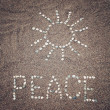 Peace word and sun symbol on the sand - toned photo. — Stock Photo #73230103