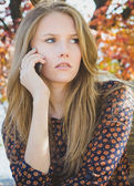 Young beautiful worried girl calling by mobile phone in park — Stock Photo