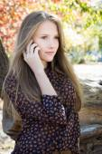 Young beautiful girl calling by mobile phone in park — Stock Photo