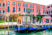 Venice cityscape - gondolas moored at pier on water canal — Stock Photo