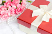 Close up of gift box with pearl necklace and pink carnation flow — Stock Photo