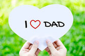 Hand holding white heart paper with I love dad text on blur gree — Stock Photo