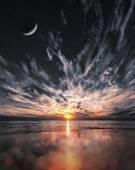 Beautiful sunset on the beach, stars and moon on the sky — Stock Photo