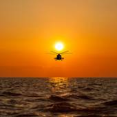 Helicopter with warm sunset as background — Stock Photo