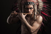 Portrait of the indian strong man posing with traditional native american make up. Playing flute — Photo