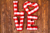 Love word of plush red letters on wood background. Full plaid textile — Stock Photo
