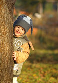 Smiling young boy behind tree — Stock Photo