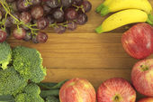 Broccoli, banana, grape, and apple on golden teak wood background — Stock Photo