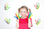 Girl painting colourful handprints — Stock Photo