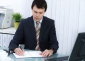 Business man in office writing in day planner — Stock Photo