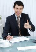 Business man in office writing in day planner shows thumb up — Stock Photo