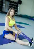 Young woman doing exercise with rubber band — Stockfoto