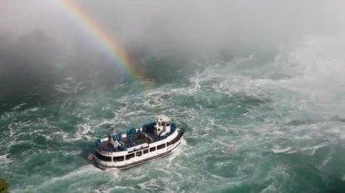 Por debajo de las Cataratas del Niágara con un barco de excursión y un arco iris en la niebla — Vídeo de Stock