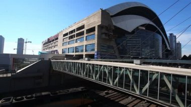 A passenger train passes the Rogers Center stadium — Vídeo de Stock