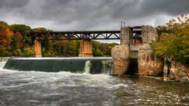Motion Controlled pan of a dam and railway bridge in autumn, a timelapse — Stock Video