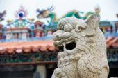 Chinese stone lion with blur temple background — Stock Photo