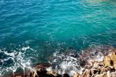 A través del agua cerca de la orilla puede ver claramente el fondo azul del mar — Foto de Stock