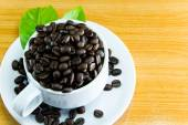 Still life Cup of coffee beans and leaves coffee on wooden table — Stockfoto