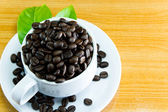 Still life Cup of coffee beans and leaves coffee on wooden table — Foto de Stock