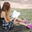 Beautiful girl reading in the park. — Stock Photo #69675591