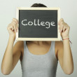 University college student holding a chalkboard saying college — Stock Photo #69934243