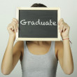 University college student holding a chalkboard saying graduate — Stock Photo #69934313