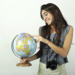 Young woman holding and pointing to globe. — Stock Photo #69934985