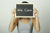Young woman holding a chalkboard saying We can — Fotografia Stock