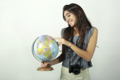 Young woman holding and pointing to globe. — Stock Photo