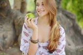 Beautiful young girl eating green apple — Stock Photo