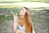 Young woman blowing soap bubbles in the air. — Stockfoto