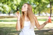 Young woman blowing soap bubbles in the air. — Stock Photo