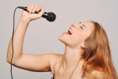 Beautiful woman singing with microphone. — Stock Photo