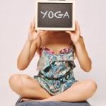Carefree woman holding a chalkboard saying yoga. — Stock Photo #75796027
