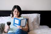 女人喝了酒,然后读一本书 — 图库照片