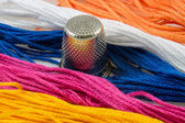 Strands of colored cotton and a thimble — Stock Photo