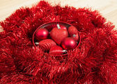 Christmas decorative red baubles and yellow toys on red sparkle background — Stock Photo