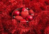 Dekorative rote Christbaumkugeln und gelbe Spielzeug auf rotem Funkeln Hintergrund — Stockfoto