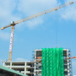 Construction site with cranes and blue sky background — Stock Photo #58008875