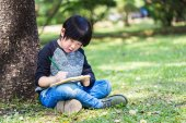 Little asian boy writing book with pencil in the park — Stock Photo