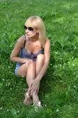 Blonde in sunglasses sitting on the grass — Stock Photo