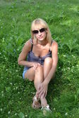 Blonde in sunglasses sitting on the grass — Stok fotoğraf
