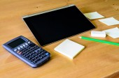 Workplace with tablet pc, calculator, pencil and sticky notes — Stock Photo