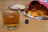 Unhealthy snacks on table with skull dice — Stockfoto