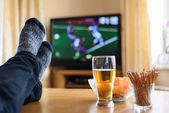 Television, TV watching (football match) with feet on table and  — Stock Photo