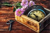 Alarm clock in box, flowers and key — Stock Photo