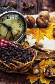 Walnuts, alarm clock and autumn leaves on the table — Stock Photo