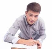νεαρός άνδρας γραψίματος σε χαρτί — Φωτογραφία Αρχείου