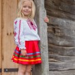 Little ukrainian girl standing near old national wooden house — Stock Photo #54042489