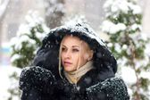 Girl in the black coat under snow fall - close up portrait — Stock Photo